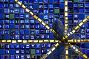 Mosaic of cobalt blue tiles with gold lines radiating through it